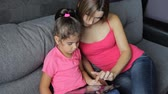woman with a child use a tablet sitting on the couch. Mother with a child use a tablet sitting on the sofa Стоковые видеозаписи