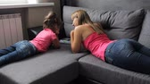 woman with a child use a tablet lying on the couch. Mother with a child use a tablet lying on the sofa Стоковые видеозаписи