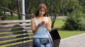 girl using smartphone in city park. woman sitting on a bench with gadgets in the Park. Стоковые видеозаписи