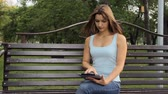 woman using tablet in city park. woman sitting on a bench with gadgets in the Park.