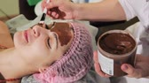 waxing : Young beautiful woman having spa procedure on her face. Chocolate spa. Chocolate wrap. Close-up