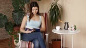 роман : Young attractive woman reading interesting book while sitting on comfortable chair in the living room.