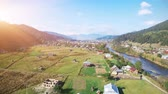 furniture : 4K Aerial Drone Footage View: Flight over sunny village with houses, forests, fields and river in sunrise soft light. Carpathian Mountains, Ukraine, Europe. Majestic nature landscape. Beauty world. Stock Footage