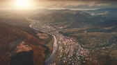 Dramatic Drone Flight over autumn village in mountain canyon. Farm meadows, orange hills, pine tree forests and river against sunset sky. Carpathians, Ukraine, Europe. Vintage retro toning filter. 4K Vídeos