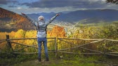 Young woman in blue jacket and pink hat standing on the edge of cliff and raising her hands up against mountain range and bright colorful autumn forest. Girl enjoying success. Toning filter. Full HD