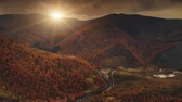 Aerial View Drone Flight over dramatic autumn sunset landscape. Small mountain village in river canyon surrounded meadows, orange hills, pine tree forests. Carpathian mountains, Ukraine, Europe. 4K