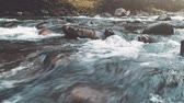 Mountain river in autumn forest. Water Slow Motion flows through massive boulders. Nature, travel, hiking, holidays concept. Dark vintage toning filter. Carpathian mountains, Ukraine, Europe. 4k