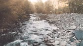 Aerial Drone Flight above mountain river in autumn forest. Water flows through cascades massive boulders. Sunset soft light landscape. Vintage toning filter. Carpathian mountains, Ukraine, Europe. 4k Vídeos