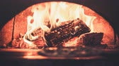 Food concept. Preparing traditional italian pizza in professional brick wood-fired oven with flame. Wood burn and the air melt from the heat. Orange color filter toning. 4k Slow Motion Parallax Effect