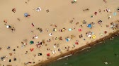 View from above, aerial view of green water sea with a sandy beach with beach umbrellas and people, kids and tourists who relax and swim.