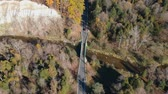 Top view of the asphalt road, the bridge and passing cars in the forest. American fall season nature at very bright sunny day.