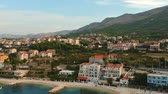 croata : Scenic aerial bird view at morning coastal village near Split in Croatia, calm and quite tourist vocational hotel seafront under green mountains in Europe. Early morning. Stock Footage