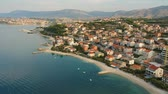 hırvat : Scenic aerial bird view at morning coastal village near Split in Croatia, calm and quite tourist vocational hotel seafront under green mountains in Europe. Early morning. Stok Video