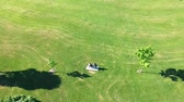 duas pessoas : Aerial flight above two young people seating on the bench in the sunny summer green grass spacey area. Couple.
