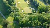 ombretti : Golf course with two player in the evening. Eye bird view from the sky. Aerial footage of park forest and golf course. Filmati Stock