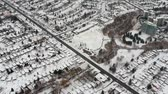 tempestade de neve : Aerial view of the roads and people houses below at snow storm, winter weather alert day. City road aerial view taken from above scenery. Top bird view suburb urban housing development. Vídeos
