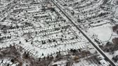явление : Aerial view of the roads and people houses below at snow storm, winter weather alert day. City road aerial view taken from above scenery. Top bird view suburb urban housing development. Стоковые видеозаписи