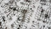 snowfall : Aerial view of the roads and people houses below at snow storm, winter weather alert day. City road aerial view taken from above scenery. Top bird view suburb urban housing development. Stock Footage