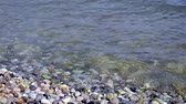 oblázek : Close up of beach made of stones or rocks and the lake waves at summer evening.