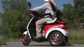 African American woman in sun glasses and hat riding electric scooter. Freedom of riding mobility vehicle along green city park on summers day. 動画素材