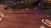 piscar : Festive Christmas wooden background. Table with New year decoration and Xmas tree with blinking lights on backdrop loop video. Winter holiday advertising concept