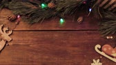 cartão de natal : Festive Christmas wooden background. Table with New year decoration and Xmas tree with blurred blinking lights on backdrop loop video. Winter holiday advertising concept