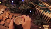 lentejoula : Delicious Christmas holiday with latte and cookies. Unrecognizable woman stirs hot drink on table near decoration from illuminated pine, gift box and gingerbread scones nearby, view from shoulder