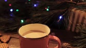 borovice : Delicious Christmas holiday with cup of latte. Just made hot drink stays on wooden table on festive background of illuminated pine, gift box and gingerbread scones nearby, close up
