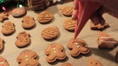 processo : Decoration process of Christmas cookies. Close up woman garnishing homemade gingerbread men with sad smile near festive illuminate pine. Family culinary and traditions concept