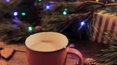 em forma de : Delicious Christmas holiday with latte. Just stired up hot drink stays on wooden table near decoration from illuminated pine, gift box and gingerbread scones nearby, close up