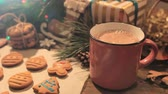 wróżka : Cocoa break during decoration process of cookies. Woman pouring hot drink into cup near homemade gingerbread scones and festive illuminate background. Christmas family culinary and traditions concept Wideo