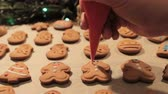 illumination : Decoration process of Christmas cookies in motion. Close up woman garnishing with icing homemade gingerbread men near festive illuminate pine. Family culinary and traditions concept