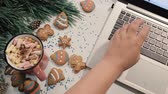 кондитерские изделия : Chatting during Christmas and New Year holidays. Unrecognizable woman typing on laptop near festive decorated pine, cookies and cup of marshmallows, top view. Greetings in social network concept Стоковые видеозаписи