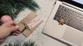 položit : Congratulation in Christmas and New Year holidays. Woman lay gift package on festive glittering table near decorated pine and laptop, top view. Greetings at office and business presents concept