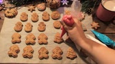 wróżka : Decoration process of Christmas cookies top view. Woman garnishing with icing homemade gingerbread fir trees near festive illuminate pine and cup of latte. Family culinary and traditions concept Wideo