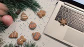 congratulação : Cookies in Christmas and New Year holidays. Unrecognizable people lay sweet scones and gift on festive glittering table near decorated pine and laptop, top view. Concept of greetings at office