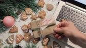 položit : Presents on Christmas and New Year holidays. Man and woman fighting for one gift laying on sweet scones near festive decorated pine and laptop, top view. Concept of greetings at office