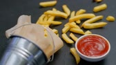 hranolky : fast food. french fries serving falls on the table surface. ketchup tomato sauce. fatty chips junk meal