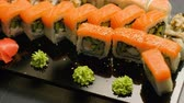delicadeza : oriental food restaurant menu. salmon sushi rolls set assortment on dark background