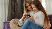 parentalidade : parenting time. family pastime. mother teaching daughter how to use smartphone Stock Footage