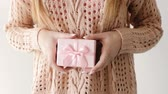 gratidão : girl hiding a present in a gift box behind her back. surprise congratulation celebration reward gratitude concept. Vídeos