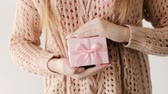 gratidão : cute little present for a female. unrecognizable woman holding a pink gift box with a bow. holiday surprise. congratulation celebration reward and gratitude concept.