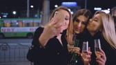 Girls night out celebration. Party mood. Ladies taking selfie, standing with champagne on the street with blur city lights. Stok Video