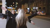 Girls night out. Ladies happy to meet their bestie on the street, hugging each other. Blur city lights background.