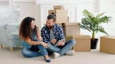 own : Young couple relaxing after moving stuff to their own apartment, sitting on floor, discussing interior design for new home. Stock Footage