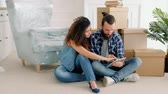 hypothek : Young couple having rest after moving stuff to their new apartment, sitting on floor, surfing internet together. Stock Footage