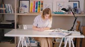 ressam : Artist at work. Young blonde woman sitting at desk sketching drawing. Project in process. Inspiration imagination creativity. Stok Video