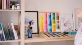 ressam : Neatly organized tidy artist studio. Artworks supplies around. Young blonde female taking watercolor sketchpad from shelf. Stok Video