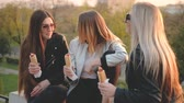 besties : Fast food. Young ladies having picnic in city park at sunset Girls eating hot dogs, chatting, laughing.