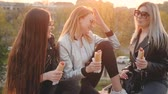 besties : Modern leisure. Young ladies having picnic in city park at sunset Girls eating hot dogs, chatting, laughing.